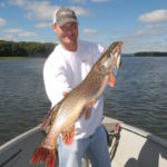 Angler holding up a large Northern Pike.
