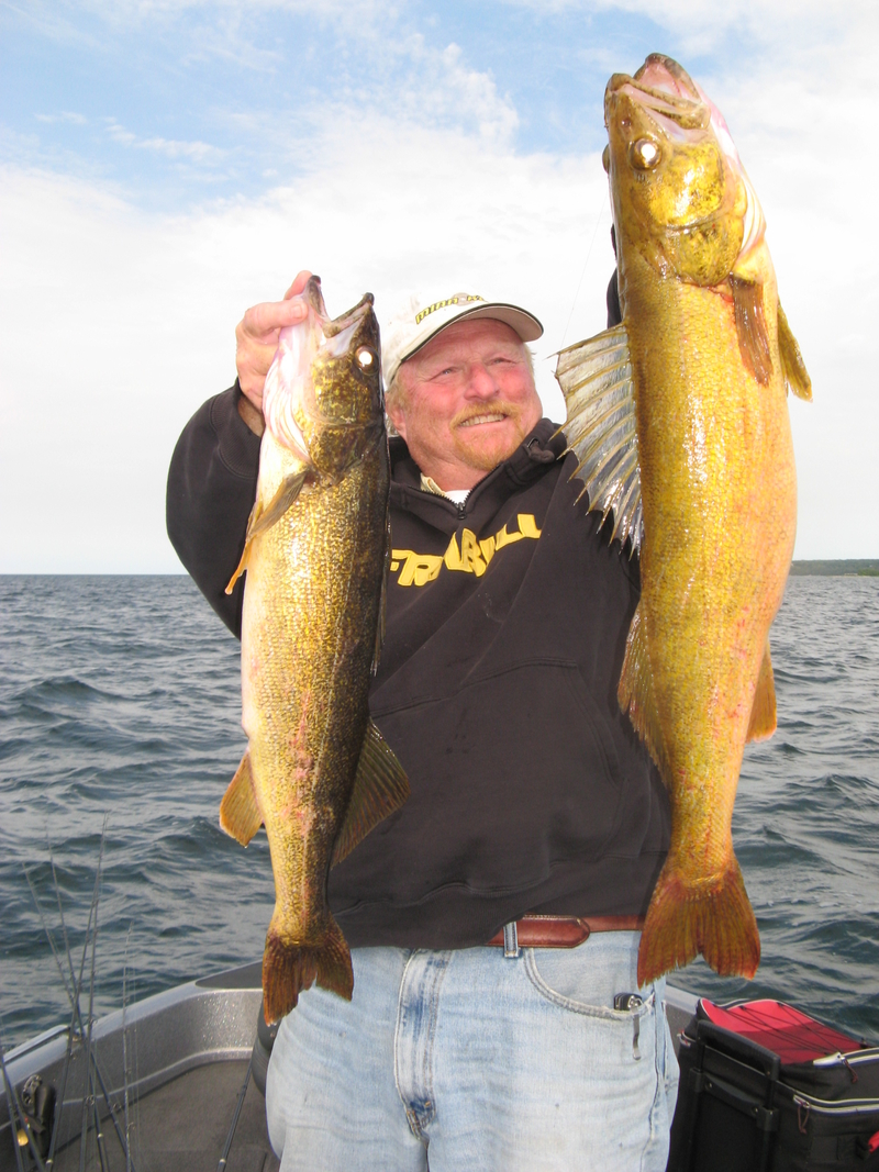 Ted Peck holding up two massive walleyes